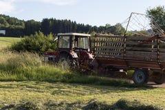 agricoltore senior che rivolta il fieno con un vecchio traktor Fotografie Stock