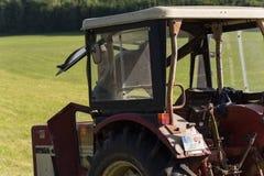 agricoltore senior che rivolta il fieno con un vecchio trattore Fotografia Stock Libera da Diritti