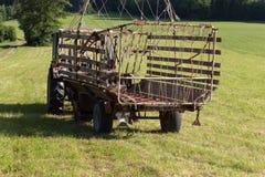 agricoltore senior che rivolta il fieno con un vecchio trattore Fotografie Stock Libere da Diritti