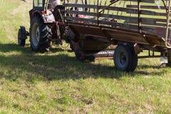 agricoltore senior che rivolta il fieno con un vecchio trattore Immagini Stock Libere da Diritti