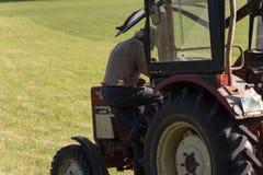 agricoltore senior che rivolta il fieno con un vecchio trattore Fotografia Stock