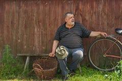 Agricoltore senior che si siede su un banco al giorno di estate Immagine Stock