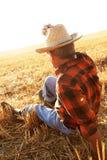 Agricoltore senior che si siede in un giacimento di grano Fotografie Stock Libere da Diritti