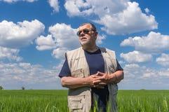 Agricoltore senior che sta i raccolti non maturi interni contro il cielo blu e nuvoloso Immagini Stock Libere da Diritti
