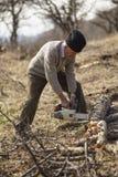 Agricoltore senior che taglia un albero a pezzi Fotografia Stock