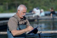 Agricoltore senior del pesce che controlla lavagna per appunti Fotografia Stock Libera da Diritti