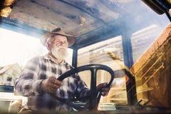 Agricoltore senior su un trattore Immagini Stock Libere da Diritti