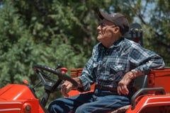 Agricoltore senior sul suo trattore Immagine Stock
