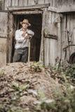 Agricoltore Shoveling il concime del cavallo Immagini Stock