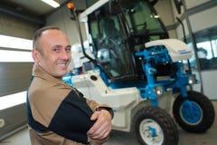 Agricoltore sicuro che ripara trattore Immagine Stock