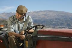 Agricoltore Sitting On Tractor contro la montagna Immagine Stock