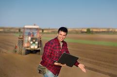 Agricoltore soddisfatto con il computer portatile ed il trattore Fotografia Stock