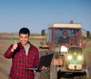 Agricoltore soddisfatto con il computer portatile ed il trattore Immagini Stock Libere da Diritti