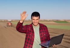 Agricoltore soddisfatto con il computer portatile ed il trattore Fotografia Stock Libera da Diritti