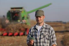 Agricoltore, soldi e raccolto, concetto agricolo Immagini Stock Libere da Diritti
