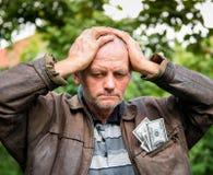Agricoltore sollecitato con soldi in suo rivestimento Immagini Stock