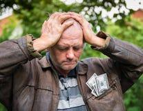 Agricoltore sollecitato con soldi in suo rivestimento Fotografia Stock