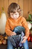 Agricoltore sorridente adorabile del bambino con il raccolto di autunno Fotografia Stock