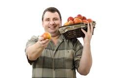 Agricoltore sorridente che offre una mela per voi Immagine Stock