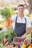 Agricoltore sorridente che passa un mazzo di carote Fotografia Stock