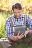Agricoltore sorridente che per mezzo di una compressa digitale Fotografia Stock Libera da Diritti