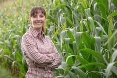 Agricoltore sorridente che posa nel campo di grano Immagine Stock