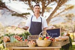 Agricoltore sorridente che presenta i prodotti locali Fotografie Stock