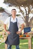 Agricoltore sorridente che sta con le mani sulle anche Fotografia Stock