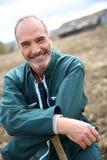 Agricoltore sorridente che sta nel campo Fotografie Stock Libere da Diritti