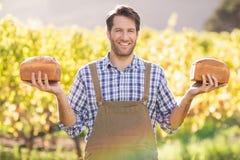 Agricoltore sorridente che tiene due pani saporiti Fotografia Stock Libera da Diritti