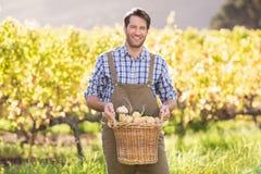 Agricoltore sorridente che tiene un canestro delle patate Fotografie Stock