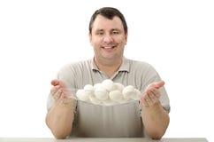 Agricoltore sorridente che tiene un canestro di vetro delle uova Fotografia Stock