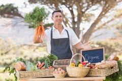 Agricoltore sorridente che tiene un mazzo di carote Immagini Stock Libere da Diritti