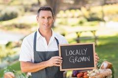 Agricoltore sorridente che tiene un segno coltivato sul posto Fotografia Stock