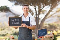 Agricoltore sorridente che tiene un segno coltivato sul posto Immagini Stock