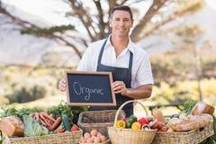 Agricoltore sorridente che tiene un segno organico Fotografia Stock