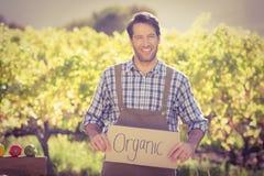 Agricoltore sorridente che tiene un segno organico Immagine Stock Libera da Diritti