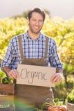 Agricoltore sorridente che tiene un segno organico Fotografie Stock