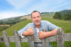 Agricoltore sorridente dal recinto Immagini Stock