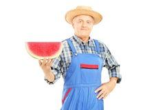 Agricoltore sorridente in denim che tengono una fetta di anguria Fotografia Stock