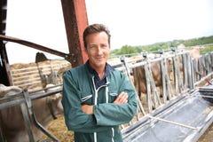 Agricoltore sorridente in granaio Fotografie Stock
