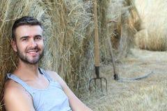 Agricoltore splendido che si rilassa su un fieno con l'agricoltura degli strumenti nei precedenti Immagini Stock