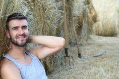 Agricoltore splendido che si rilassa su un fieno con l'agricoltura degli strumenti nei precedenti Fotografia Stock Libera da Diritti