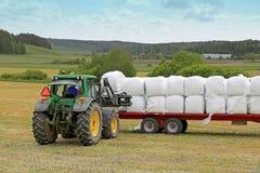 Agricoltore Stacks su silaggio con Front Loader John Deere 6330 Tracto Fotografia Stock