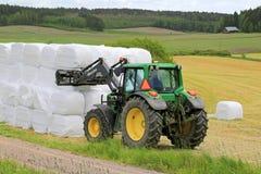 Agricoltore Stacks su silaggio con Front Loader John Deere 6330 Tracto Immagine Stock
