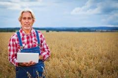 Agricoltore Standing In un giacimento di cereale Fotografie Stock