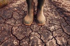 Agricoltore in stivali di gomma che stanno sulla terra del suolo asciutto fotografia stock libera da diritti