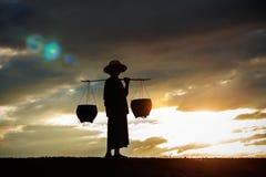 Agricoltore su un campo al tramonto Fotografia Stock