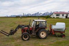 Agricoltore su un trattore che avvolge hey le balle Fotografia Stock