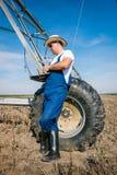 Agricoltore sugli impianti di irrigazione Immagini Stock